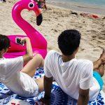 Tourists with a pink flamingo floatie on Waikiki Beach, Oahu, Hawaii. *** Local Caption ***  travel Hawaii beach Waikiki Oahu vacation tourism tourist tourists floatie flamingo selfie cell phone cellphone mobile phone couple