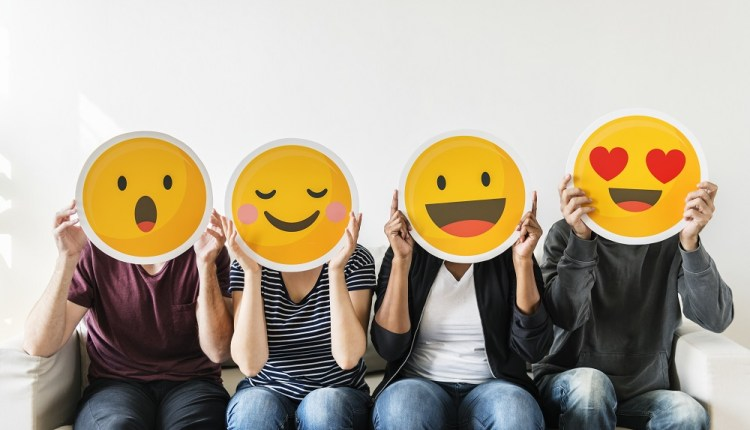 Diverse people holding emoticon